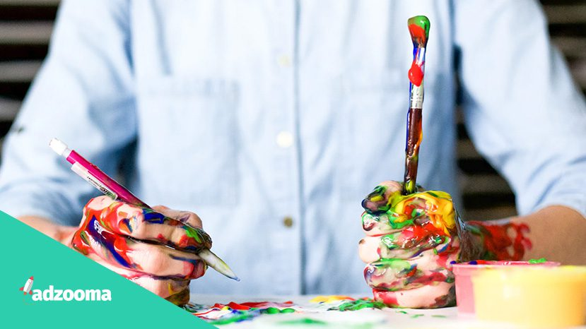 A creative man holding a pen and paintbrush covered in paint